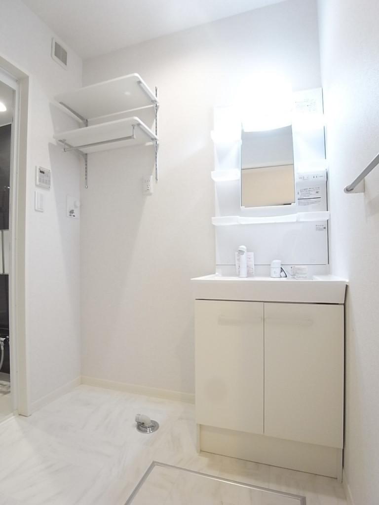 洗面脱衣所。洗濯機置き場の上には便利にお使いいただける棚とバーが付いています!