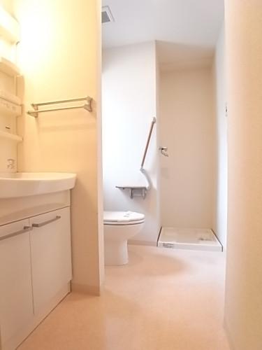 洗面脱衣所。手前から洗面台、トイレ、洗濯機置場。浴室は右手にございます!
