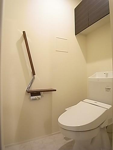 温水洗浄便座付きのトイレ。上部棚にはペーパー類のストックを。