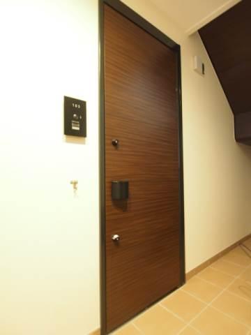 落ち着いた色合いの玄関ドア。鍵はダブルロックです。